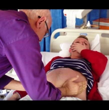 Доктор с ръце стиска корема на тази бременна жена